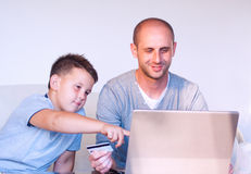 Jeune faher avec l'enfant achetant en ligne à la maison image libre de droits