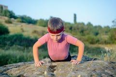 Jeune faire sportif de garçon soulèvent sur Boulder photo libre de droits