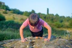 Jeune faire sportif de garçon soulèvent sur Boulder images libres de droits