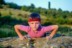 Jeune faire sportif de garçon soulèvent sur Boulder images stock