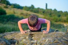 Jeune faire sportif de garçon soulèvent sur Boulder Photographie stock