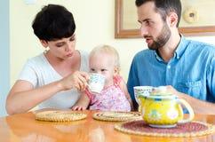 Jeune famille à la maison le week-end Thé potable de famille Photo libre de droits
