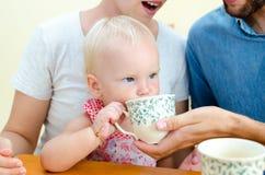 Jeune famille à la maison le week-end Thé potable de famille Images stock