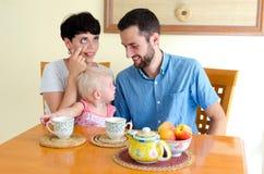 Jeune famille à la maison le week-end Thé potable de famille Image libre de droits