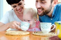 Jeune famille à la maison le week-end Thé potable de famille Photographie stock libre de droits