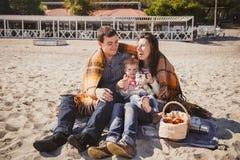 Jeune famille affectueuse heureuse avec le petit enfant au pique-nique, appréciant le temps à la plage se reposant et étreignant  Photographie stock
