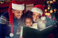 Jeune famille afro-américaine lisant ensemble des contes de fées de Noël Image stock