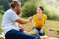 Jeune famille agréable partageant la nourriture sur le pique-nique Photos stock