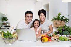 Jeune famille asiatique utilisant l'ordinateur ensemble à la maison photos libres de droits