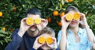 Jeune famille avec badiner orange de tranches banque de vidéos