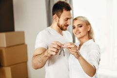 Jeune famille avec des clés à la nouvelle maison photos stock
