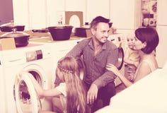 Jeune famille avec des enfants choisissant la machine à laver Image libre de droits