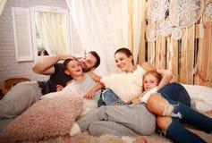 Jeune famille avec deux enfants détendant ensemble à la maison sur le lit Photographie stock