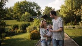 Jeune famille avec la fille marchant sur l'herbe verte en parc banque de vidéos