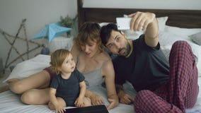 Jeune famille avec la petite fille mignonne prenant le portrait de selfie sur l'appareil-photo de smartphone se reposant dans le  Images libres de droits