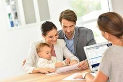 Jeune famille avec le bébé à l'agence immobilière photographie stock