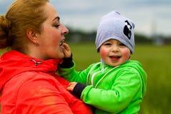 Jeune famille avec un enfant marchant dans le domaine Photographie stock libre de droits