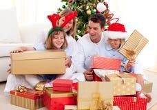 Jeune famille ayant l'amusement avec des cadeaux de Noël Photos libres de droits