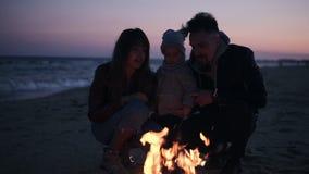 Jeune famille caucasienne s'asseyant par le feu de camp et appréciant la proximité dehors en passant la soirée ensemble dessus banque de vidéos