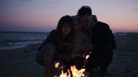 Jeune famille caucasienne squating à côté du feu de camp et appréciant la proximité Embrassant leur fille de chacun des deux côté banque de vidéos