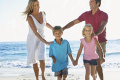 Jeune famille courant le long de Sandy Beach On Holiday photo stock