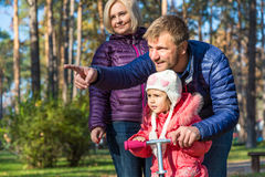 Jeune famille dans Forest Pointing automnal Photographie stock