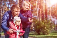 Jeune famille dans Forest Pointing automnal Photographie stock libre de droits