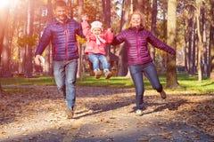 Jeune famille dans Forest Running automnal Images libres de droits