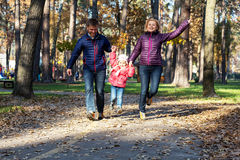 Jeune famille dans Forest Running automnal Photo stock