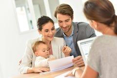 Jeune famille dans l'agence immobilière achetant la nouvelle maison Photographie stock libre de droits