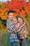 Jeune famille dans la forêt d'automne Photographie stock