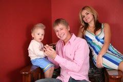 Jeune famille dans le fauteuil Photos stock