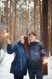 Jeune famille dans une forêt d'hiver avec des cierges magiques Image stock