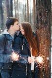 Jeune famille dans une forêt d'hiver avec des cierges magiques Photos stock
