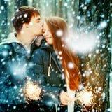 Jeune famille dans une forêt d'hiver avec des cierges magiques Photo libre de droits