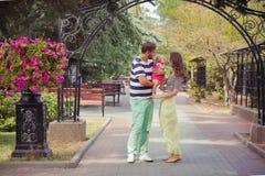 Jeune famille de la mère de père et de la fille d'enfant de bébé marchant et se tenant sur le parc de rue de ville d'été près du  Photographie stock libre de droits