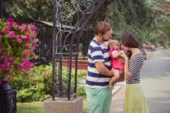 Jeune famille de la mère de père et de la fille d'enfant de bébé marchant et se tenant sur le parc de rue de ville d'été près du  Photo stock