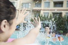 Jeune famille de sourire éclaboussant et jouant dans la piscine Images stock