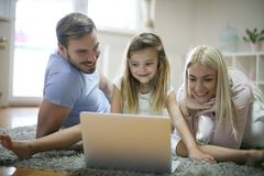 Jeune famille de sourire utilisant l'ordinateur portable photographie stock