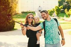 Jeune famille faisant la photo de selfie sur l'appareil-photo de mouvement en parc d'EUR Photo libre de droits