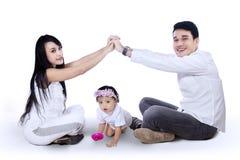 Jeune famille faisant le signe à la maison Image stock
