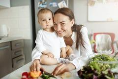 Jeune famille gaie de la mère et du bébé garçon nouveau-né étreignant, sourire, posant pour la photo de famille dans la cuisine f Photos libres de droits
