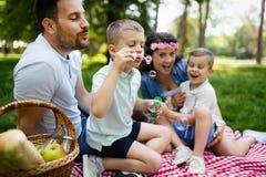 Jeune famille heureuse appréciant le pique-nique en nature photo libre de droits