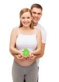 Jeune famille heureuse attendant l'enfant avec la maison Image stock