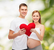 Jeune famille heureuse attendant l'enfant avec le grand coeur Image stock