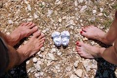 Jeune famille heureuse attendant le bébé, l'amour et le bonheur Futurs pieds de maman et de papa avec de petites chaussures de bé Images stock