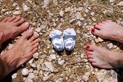 Jeune famille heureuse attendant le bébé, l'amour et le bonheur Futurs pieds de maman et de papa avec de petites chaussures de bé Photo stock