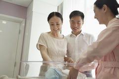 Jeune famille heureuse avec l'infirmière regardant vers le bas leur nouveau-né dans la crèche d'hôpital Photos stock
