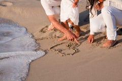 Jeune famille heureuse avec le descendant sur la plage en été photos libres de droits