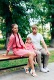 Jeune famille heureuse avec le petit beau bébé avec des yeux bleus marchant en parc d'été au coucher du soleil maman et petit des Photos libres de droits